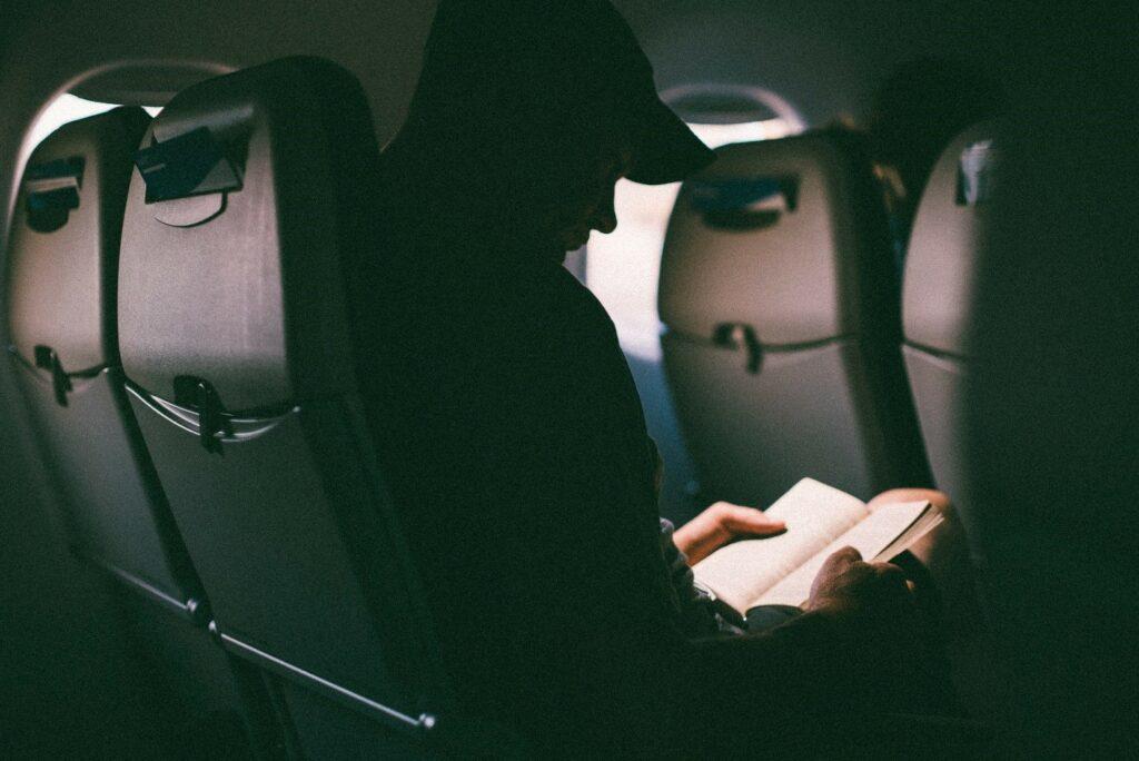 Man reading book in long flight